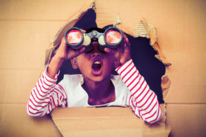 Boy popping out of cardboard box to discover new adventure