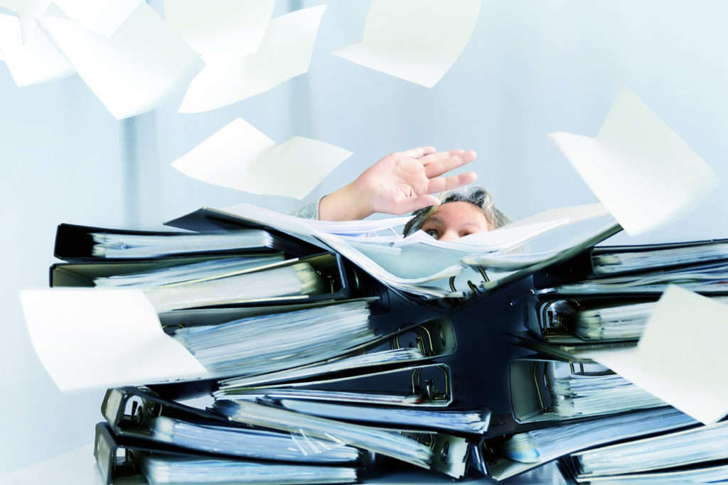 Desperate woman behind stacks of binders and flying papers